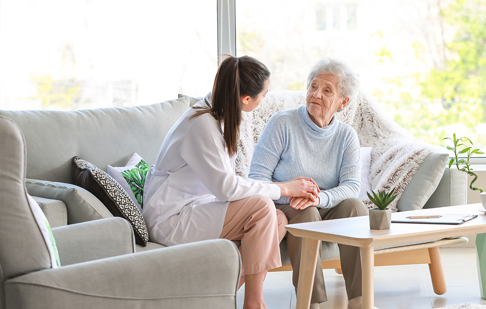 doctor speaking to her eldery patient on a couch