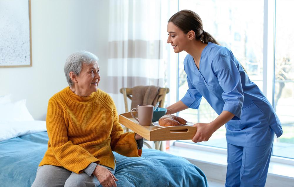 Nurse bringing lunch to her elderly patient