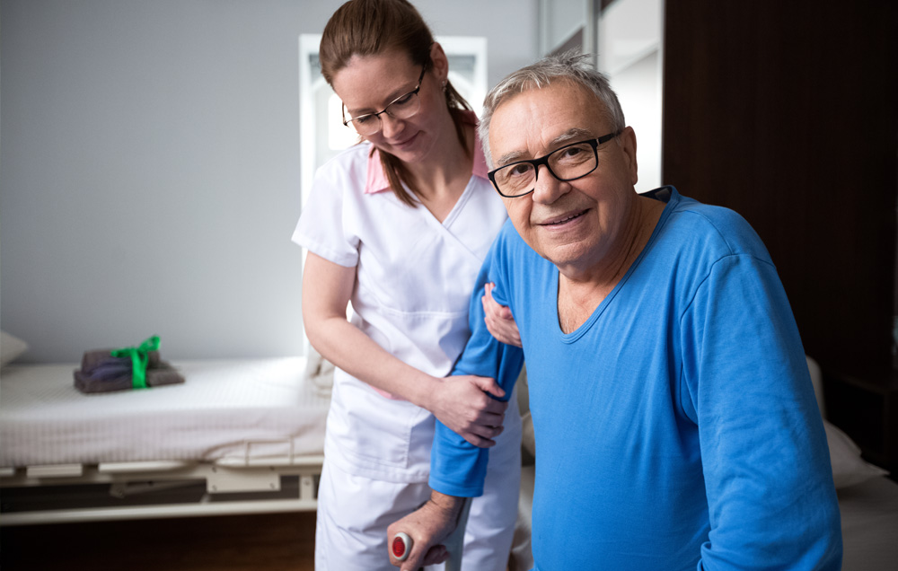 nurse helping her patient stand up and walk | Transitional Care Services | Miami FL 33165 | call 305-520-5585