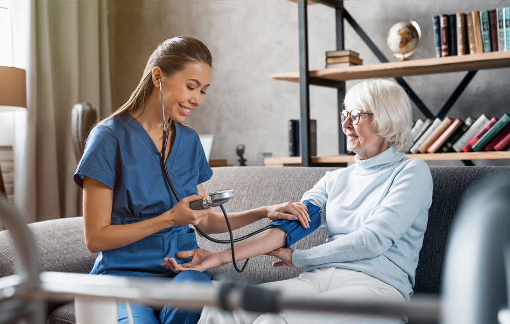Nurse taking blood pressure of her patient on her couch